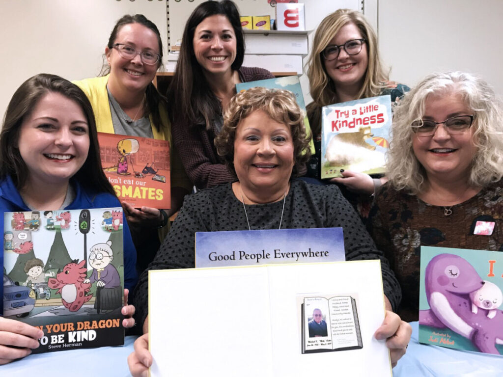 Pictured from left front row:  Carly Givens Goddard, Susie Baker and Cathy Givens. Back row from left:  Amber Baker, Gina Berisford and Lauren Baker. They are holding the books bought for the school in Mike's memory.