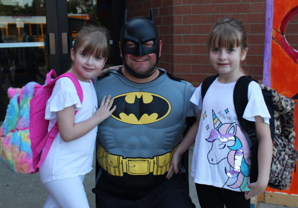 Batman welcomes twin sisters Lily (left) and Faith (right) Goodnight to McNinch Primary for their second grade year.