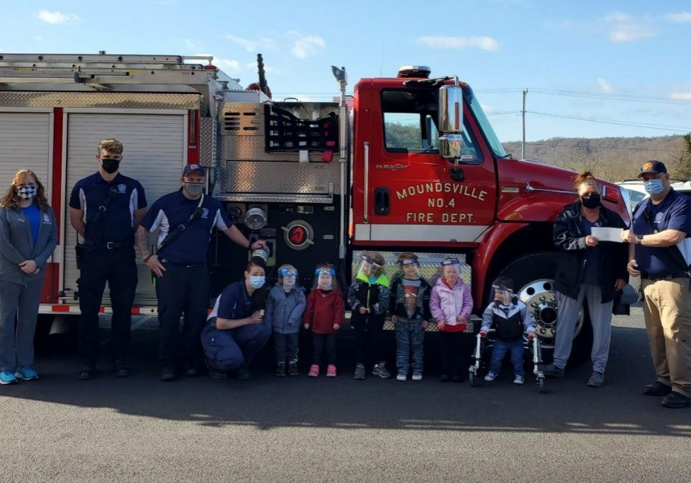 Teachers, students, and firefighters standing in front of a red firetruck